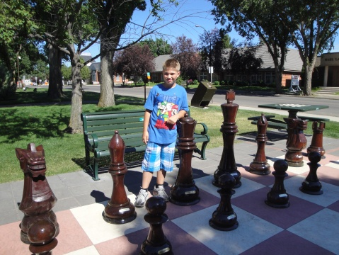 Grandson playing a giant game of chess near the library