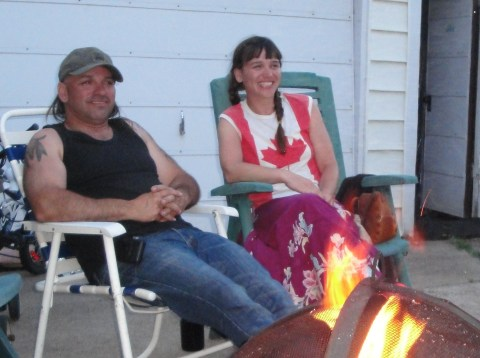 Sister and brother visiting around the fire.