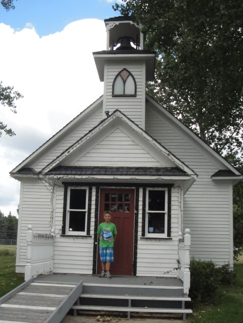 Grandson by a prairie church built in 1924