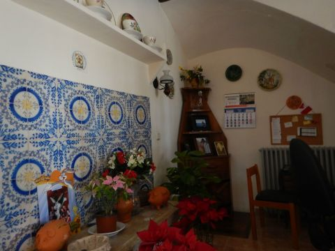 Sitting room with original tiles on the wall. A well is under the corner cabinet.